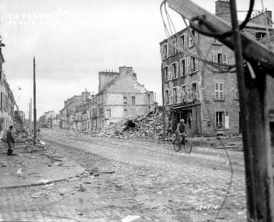 Sous les yeux d'un civil, un soldat américain traverse les ruines de Cherbourg à bicyclette