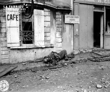 Soldat allemand mort (cadavre) sur un trottoir de Cherbourg devant la devanture du café Estasse.
