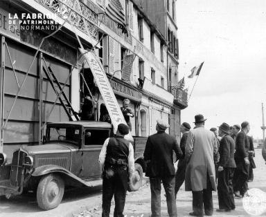Le 28 juin 1944, des Cherbougeois décrochent un panneau allemand (inscription : SOLDATENHEIMES).
