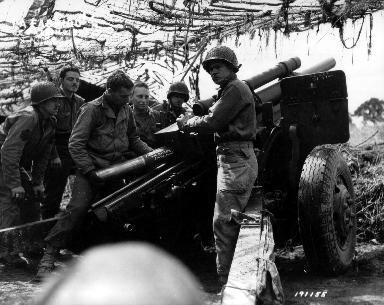 Artilleurs américains derrière un obusier.