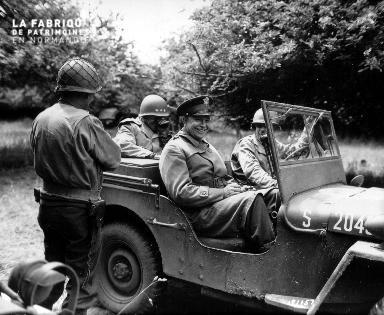 Le 4 juillet 1944 à Huanville, le général Eisenhower sourit à bord d'une jeep américaine.