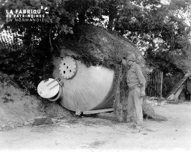 Soldat américain proche d'une cuve recouverte de toile de camouflage à Bricquebec
