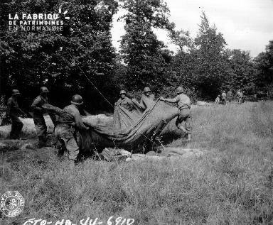 Soldats américains dans un champ ajustant une toile de camouflage