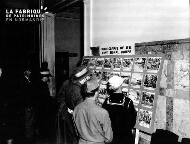 Des soldats et marins américains regardent une planche contact de photographies relatives à la guerre dans le Pacifique.