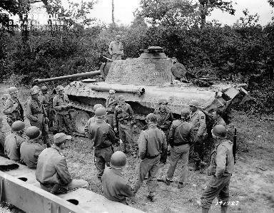 Le 19 juillet 1944, soldats américains autour d'un char de combat aux alentours de Pont Hébert.