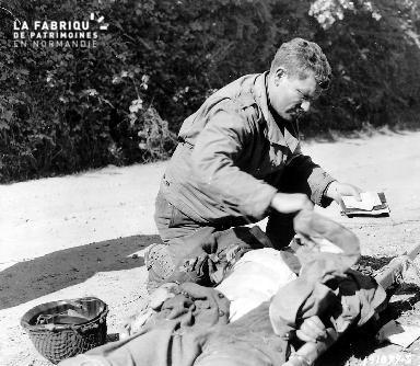 Le 28 juillet 1944, le Lieutenant John G. Burkhalter, Chaplain à la 1st US ID récupère les effets personnels d'un soldat allemand mort pour les renvoyer à la famille (AD50)