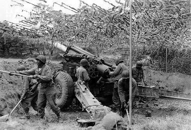 Artilleurs noirs américains derrière un obusier.