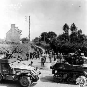 Prisonniers allemands et colonne de blindés américains