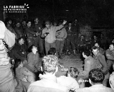 Prés de Landelles, des GI écoutent l'acteur Edward G. Robinson en tournée en Normandie (Normandy World Premier)