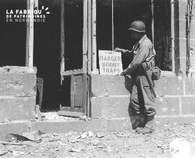 """Au cœur des ruines, un sapeur appose une pancarte """"danger booby traps"""" le 11 août 1944"""