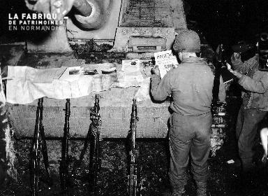 Soldats américains lisant des journaux allemands devant un char d'assaut.