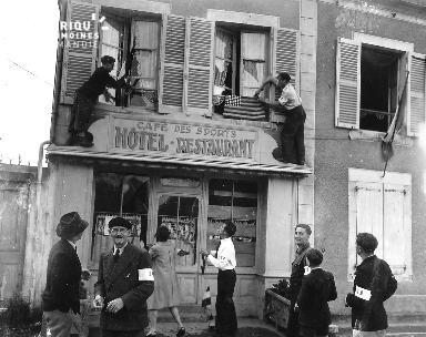 Des Normands accrochent des drapeaux aux fenêtres de la façade d'un hôtel-restaurant  au Molay Littry le 5 juillet 1944.