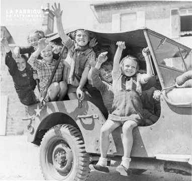 Enfants à bord d'une jeep américaine