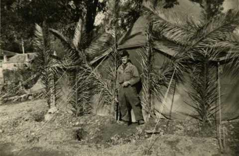 Portrait d'un soldat devant une tente militaire