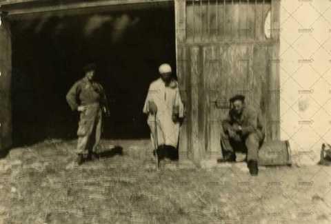 Algérien avec une canne, accompagné de deux soldats français