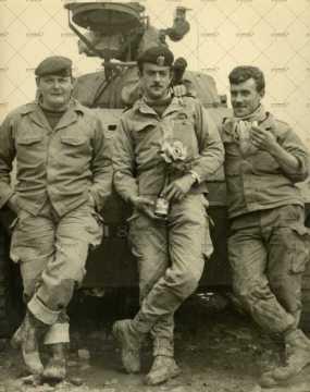 Trois soldats français devant un char militaire