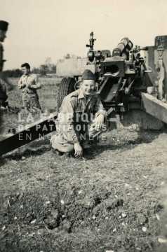 Soldat posant devant un canon m2 de 105 mm durant un entrainement