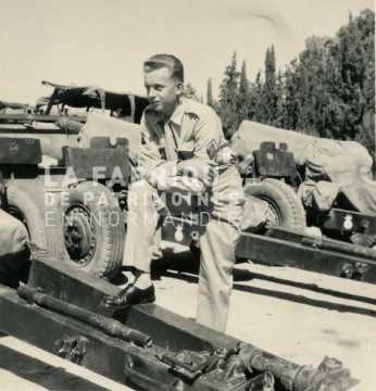 Soldat français posant en tenue de sortie entre plusieurs canons m2 de 105 mm