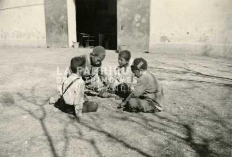 Enfants algériens jouant dans une cour