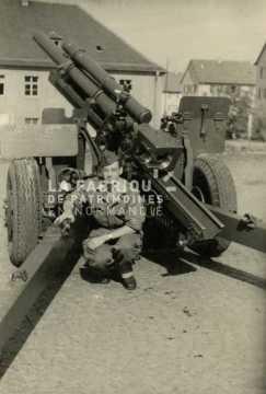 Soldat français posant devant un canon de 105 mm