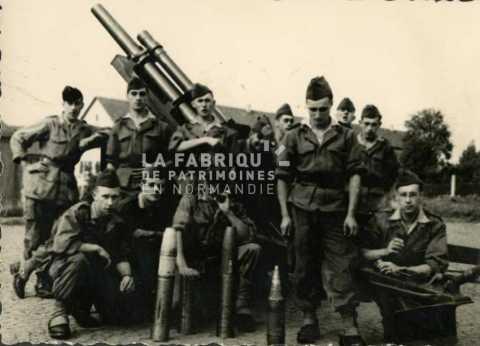 Soldat français posant devant un canon et ses munitions