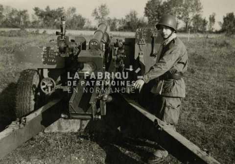 Soldat devant un canon de 105 mm M2 durant son service militaire