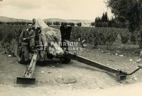 Soldat français posant devant un canon M2  de 105 mm