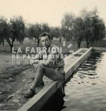 Soldat français assis devant un réservoir d'eau (piscine?) en Algérie