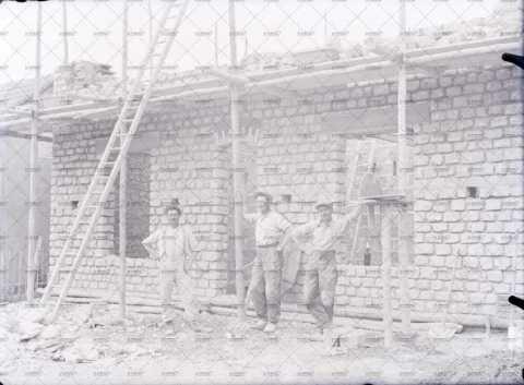 Ouvriers devant une maison en construction