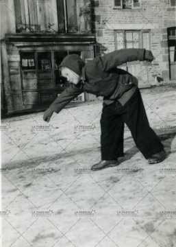 Un enfant jouant dans les rues de Pont d'Ouilly
