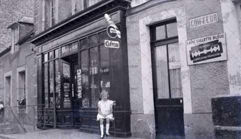 Enfant devant la devanture de l'épicerie