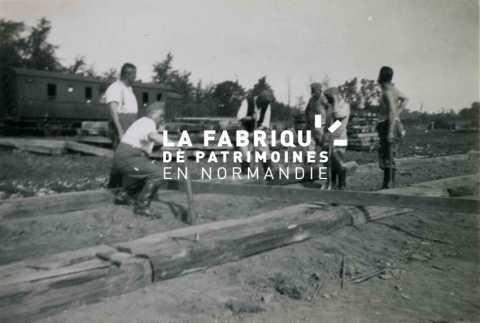 Charpentiers, pionniers de la Wehrmacht lors de travaux de construction d'un quai de déchargement proche de la gare Bayeux