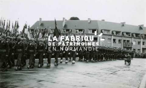 Soldats américains défilant dans les rues d'Avranches lors d'une parade célébrant la libération, sous les yeux des habitants à leurs fenêtres.