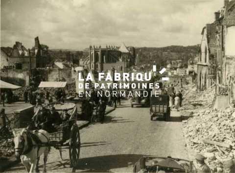 Civils et véhicules circulant dans une rue endommagée après les bombardements de juin 1940.